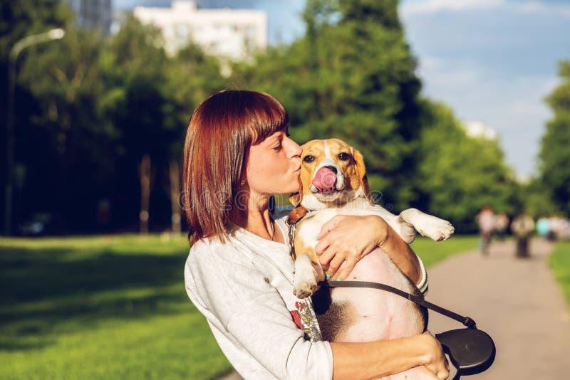 Portret van jonge vrouw die haar leuke brakhond kussen Liefde, gelukkig, het kussen puppy stock foto's