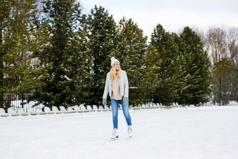 Portret van jonge vrouw die op ijs skateboardt met schaatsen buiten royalty-vrije stock fotografie