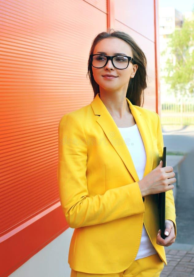 Portret van jonge vrouw in glazen, geel kostuum met omslag stock afbeeldingen