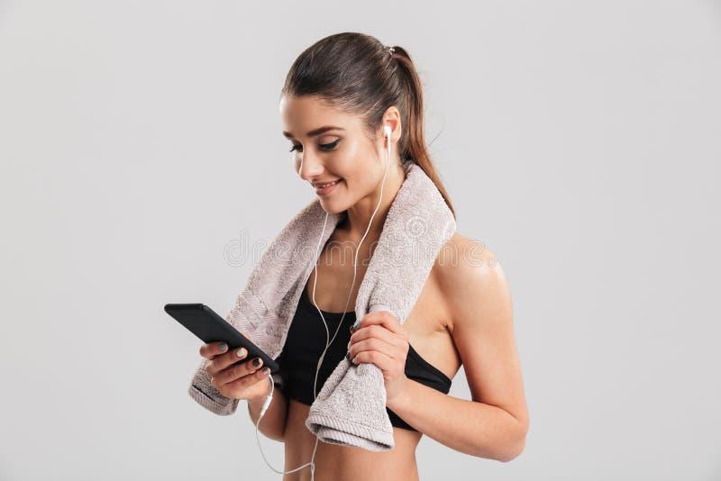 Portret van jonge vrouw in gymnastiek het stellen met handdoek op hals en lis stock foto