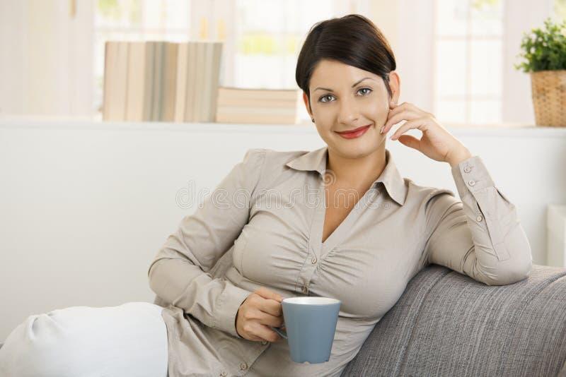 Portret van jonge vrouw het drinken koffie stock fotografie