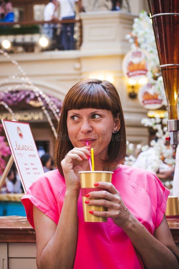 Portret van jonge vrouw het drinken soda bij winkelcomplex stock fotografie