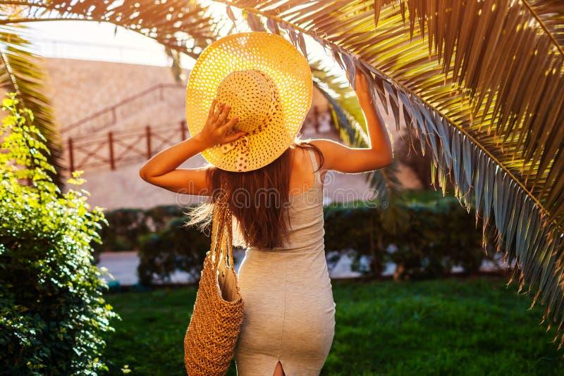 Portret van jonge vrouw in het palmblad van de hoedenholding in hotelyard royalty-vrije stock foto