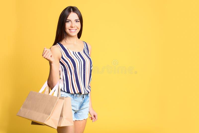 Portret van jonge vrouw met document zakken op gele achtergrond stock fotografie