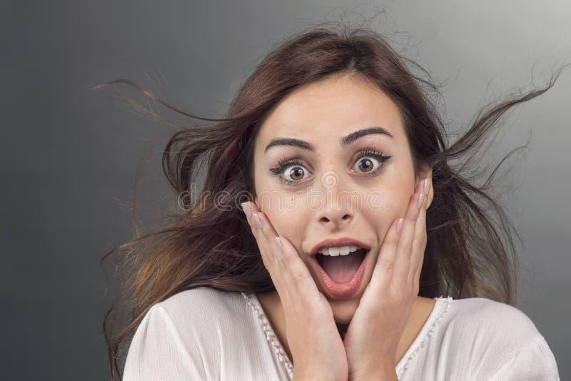 Portret van jonge vrouw met geschokte gelaatsuitdrukking stock afbeeldingen