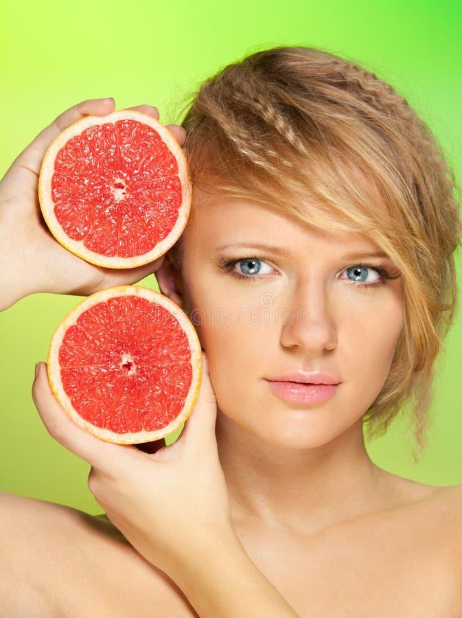 Portret van jonge vrouw met grapefruit stock afbeelding