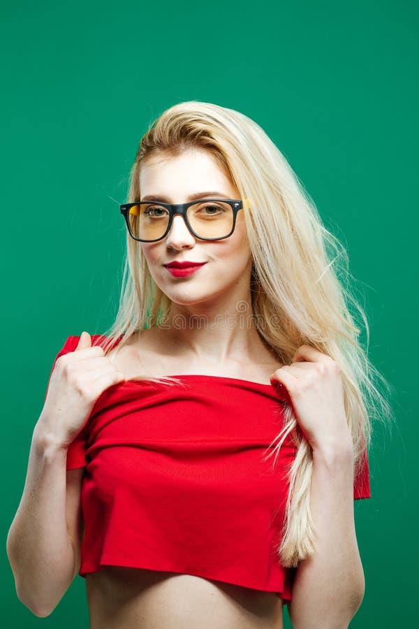 Portret van Jonge Vrouw met Lang Blond Haar, Oogglazen en Naakte Schouders in Rode Bovenkant het Stellen op Groene Achtergrond in royalty-vrije stock foto's