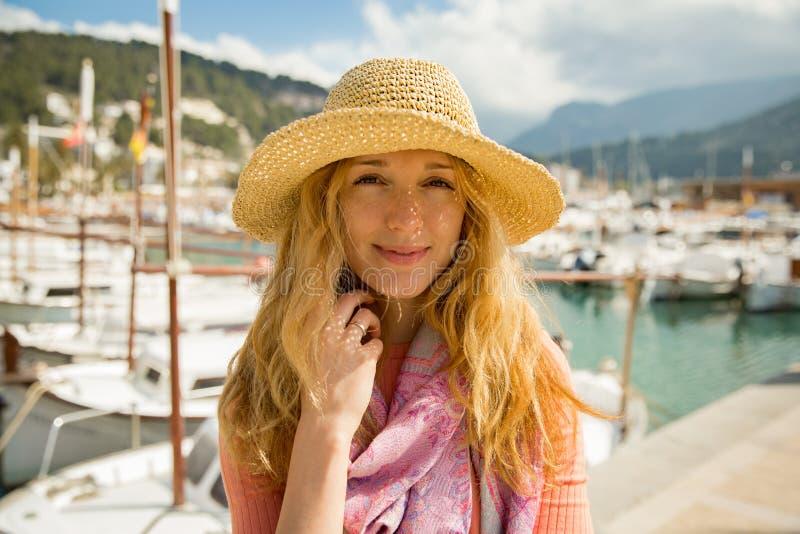 Portret van jonge vrouw met licht krullend haar in strohoed stock foto's