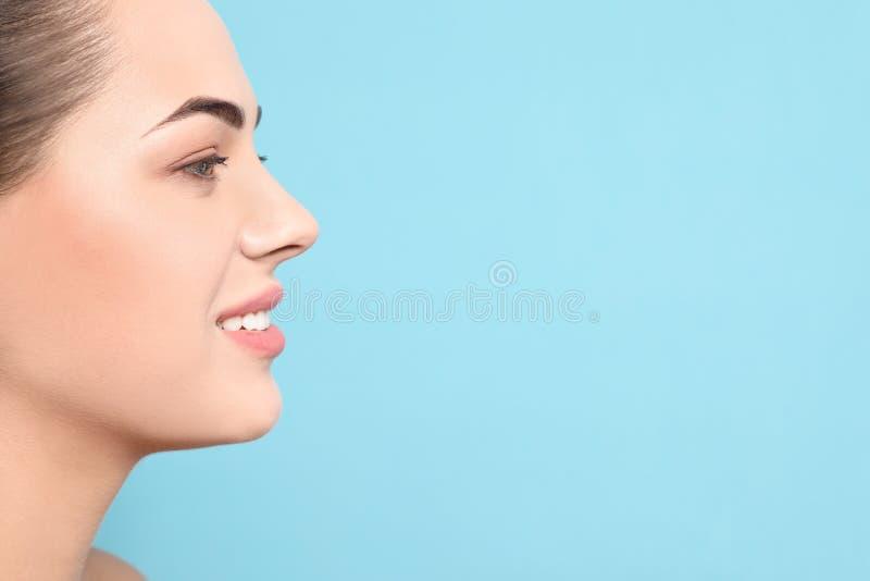 Portret van jonge vrouw met mooi gezicht en natuurlijke make-up op kleurenachtergrond, close-up stock afbeelding