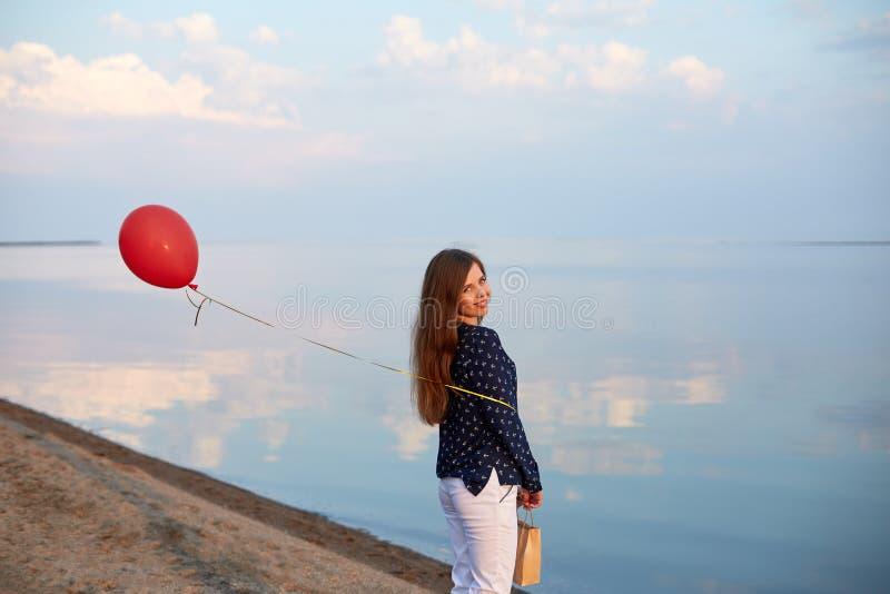 Portret van jonge vrouw met rode luchtballon en huidige zak dichtbij de kalme overzeese of meerkust De wolken worden weerspiegeld royalty-vrije stock foto's