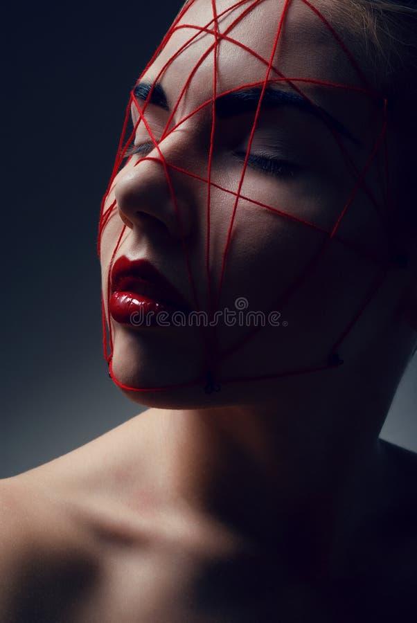 Portret van jonge vrouw met rood Web op gezicht royalty-vrije stock foto's