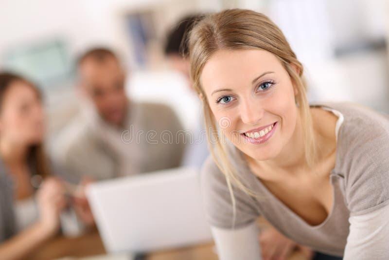 Portret van jonge vrouw op kantoor met medewerkers royalty-vrije stock afbeeldingen