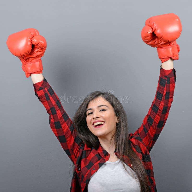 Portret van jonge vrouw in vrijetijdskleding en handen omhoog in lucht met bokshandschoenen die als winnaar tegen grijze achtergr royalty-vrije stock fotografie