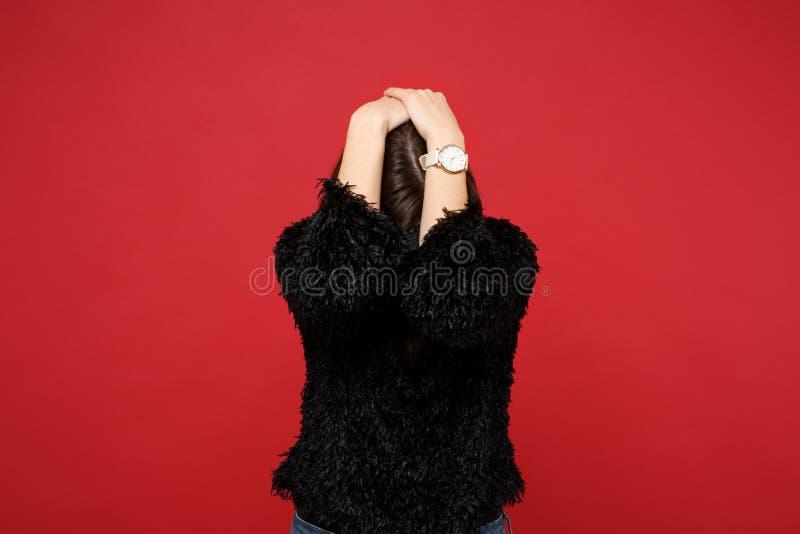 Portret van jonge vrouw in zwarte bontsweater die handen op verminderd hoofd, verbergen zetten geïsoleerd op heldere rode muur stock afbeeldingen