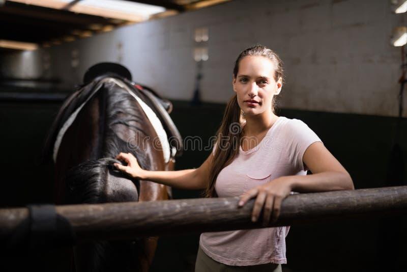 Portret van jonge vrouwelijke jockey die zich door paard bevinden royalty-vrije stock afbeelding