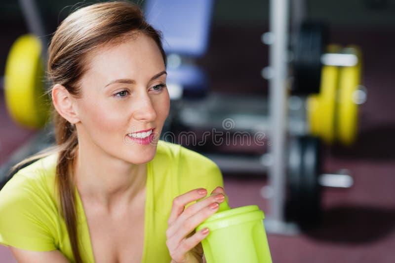 Portret van jonge vrouwen met een fles water in haar hand en opzij het kijken royalty-vrije stock afbeeldingen