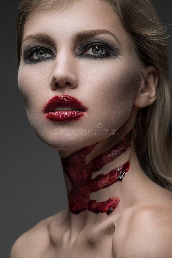 Portret van jonge vrouwen met het bloed van make-upnd op de hals royalty-vrije stock foto