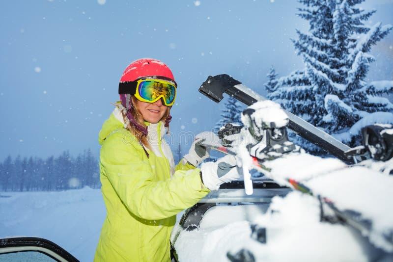 Portret van jonge vrouwen vastmakende skis op autodak stock foto