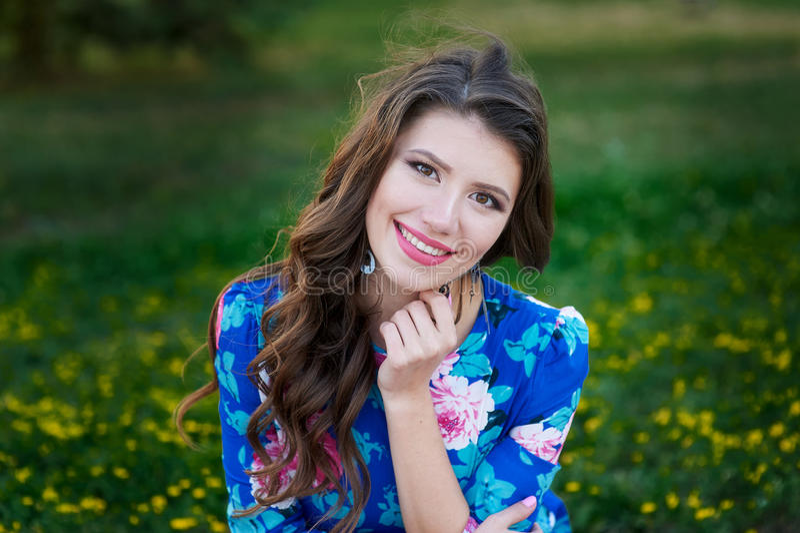 Portret van jonge vrouwenrust in het park die op het gras glimlachen stock foto