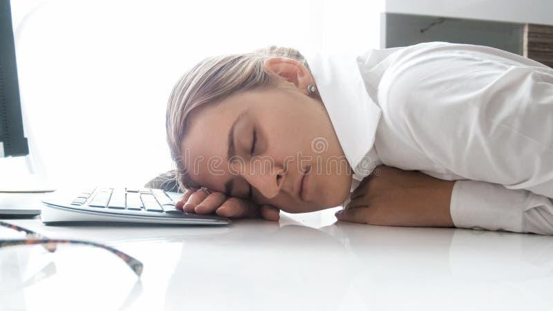 Portret van jonge vrouwenslaap op bureau op kantoor stock foto's