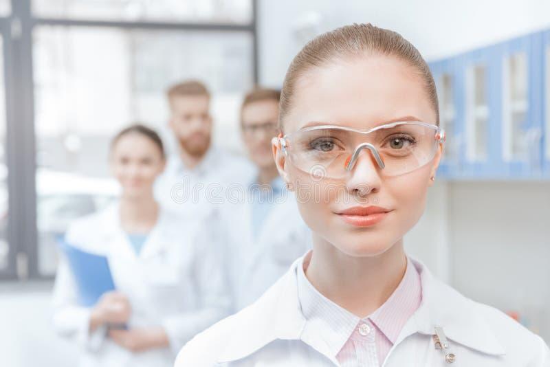 Portret van jonge vrouwenwetenschapper in laboratoriumlaag en veiligheidsbrillen het glimlachen royalty-vrije stock fotografie