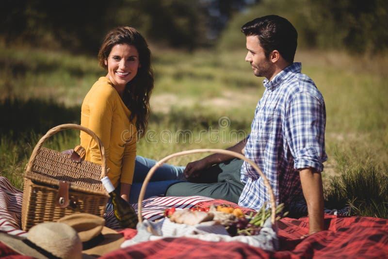 Portret van jonge vrouwenzitting met vriend op picknickdeken stock foto