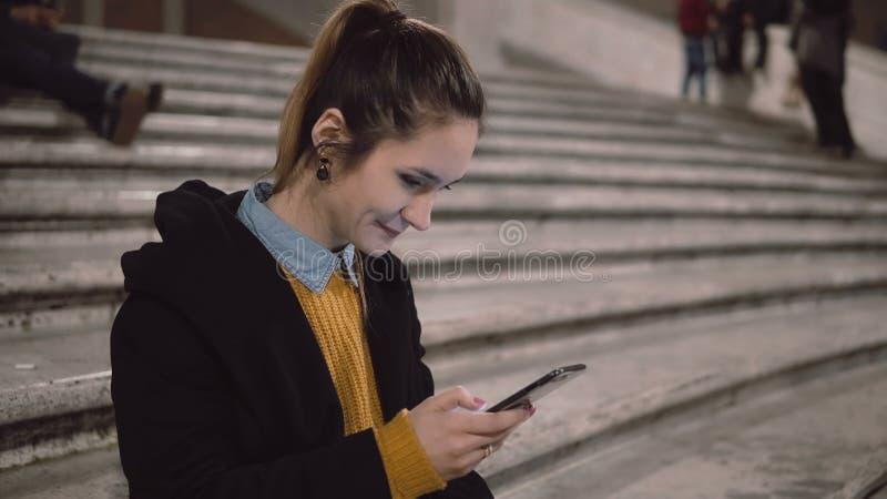 Portret van jonge vrouwenzitting op ladder en holdingssmartphone Het meisje gebruikt touchscreen voor doorbladert Internet royalty-vrije stock afbeelding