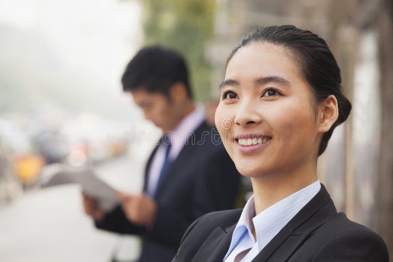 Portret van jonge, zekere onderneemster die weg en in de straat, Peking, China glimlachen kijken royalty-vrije stock afbeeldingen