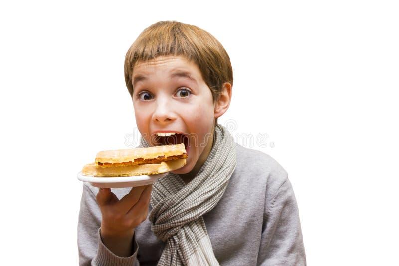 Portret van jongen die die een wafel eten - op wit wordt geïsoleerd royalty-vrije stock foto's