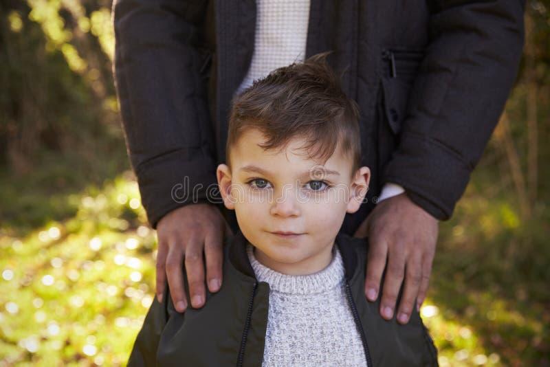 Portret van Jongen met Vader Standing In Autumn Garden royalty-vrije stock afbeeldingen