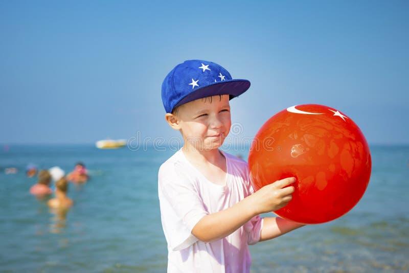 Portret van jongen op strand Weinig jongen in GLB met een opblaasbare bal tegen het blauwe overzees op duidelijke, zonnige de zom stock fotografie