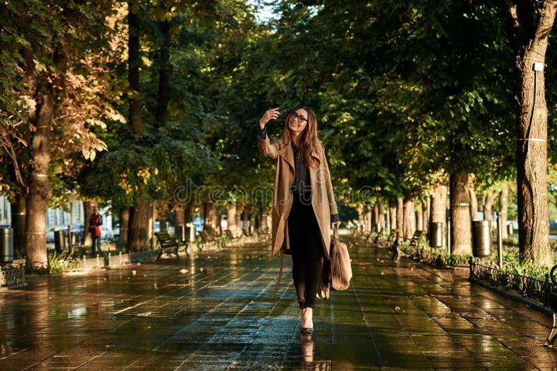 Portret van joyous vrouw die celtelefoon met behulp van terwijl het lopen door lege steeg royalty-vrije stock foto's