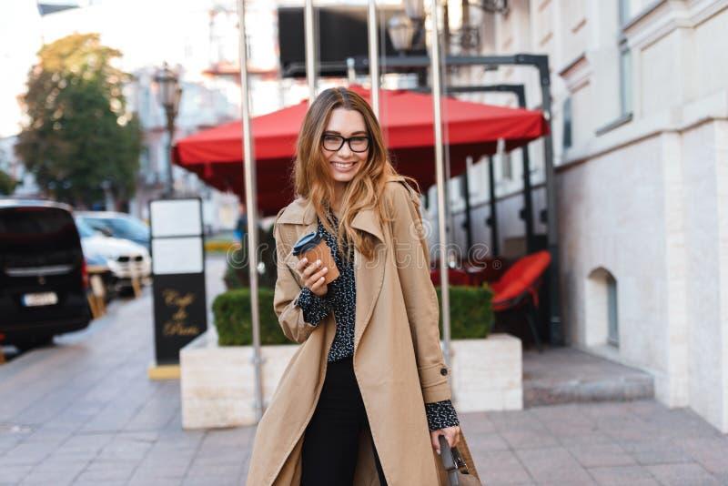 Portret van joyous vrouw die meeneemkoffie drinken terwijl het lopen door stadsstraat stock fotografie