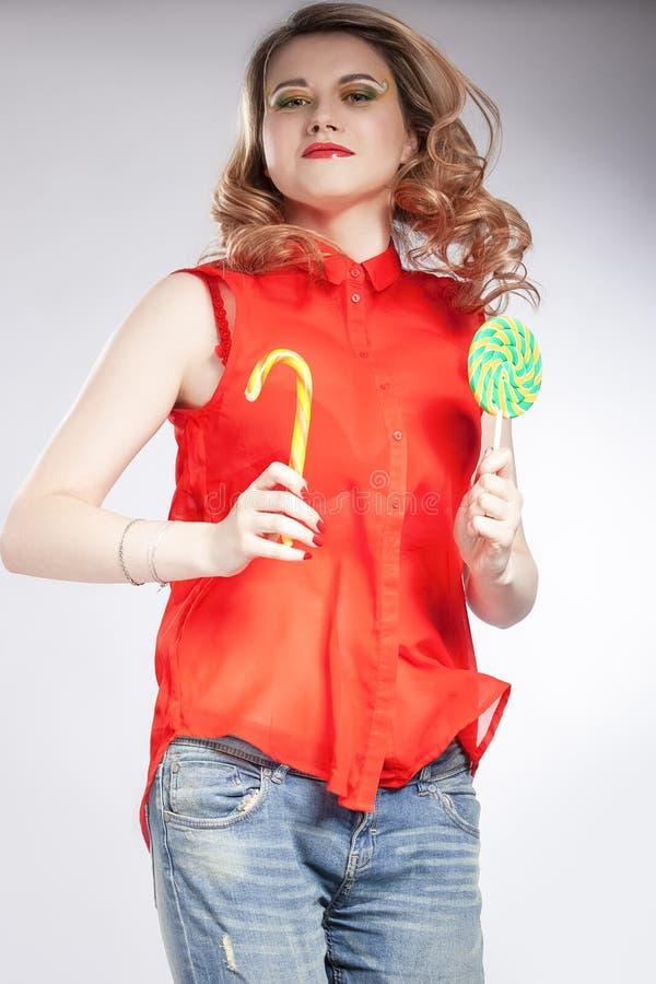 Portret van Jumping Sexy Alluring Caucasian Blond Girl met Round Lollipop en Sugar Stick Posing in Studio Tegen White stock afbeelding