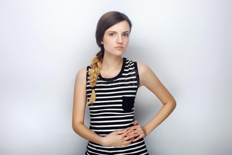 Portret van kalme jonge mooie vrouw in gestreept overhemd wat betreft haar elleboog het stellen voor modeltests tegen studioachte royalty-vrije stock afbeelding
