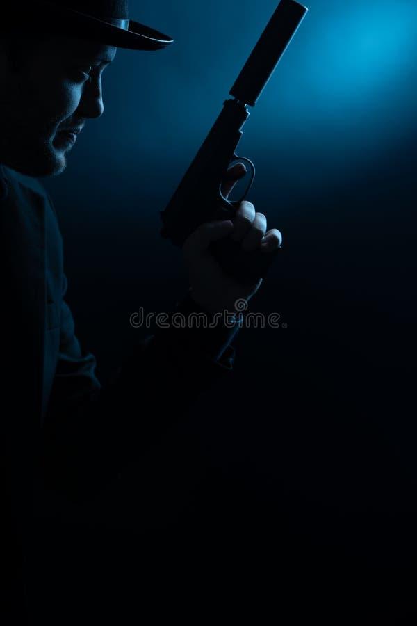 Portret van kant van de mens in zwarte hoed met pistool stock afbeelding