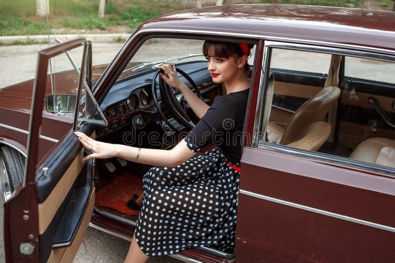 Portret van Kaukasisch mooi jong meisje in zwarte uitstekende kleding die in een retro auto zit royalty-vrije stock foto's