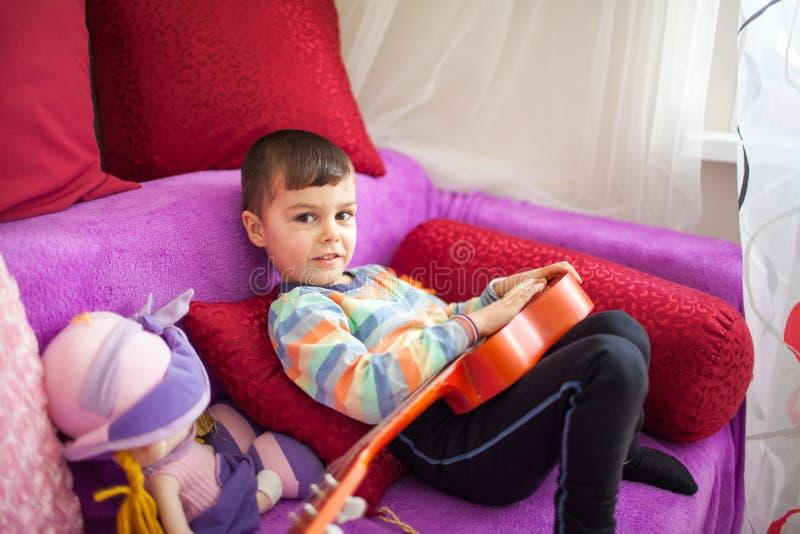 Portret van Kaukasisch weinig charmante jongen met een stuk speelgoed gitaar in selectieve nadruk stock fotografie