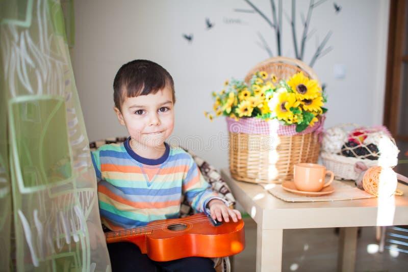 Portret van Kaukasisch weinig charmante jongen met een stuk speelgoed gitaar in selectieve nadruk stock foto's