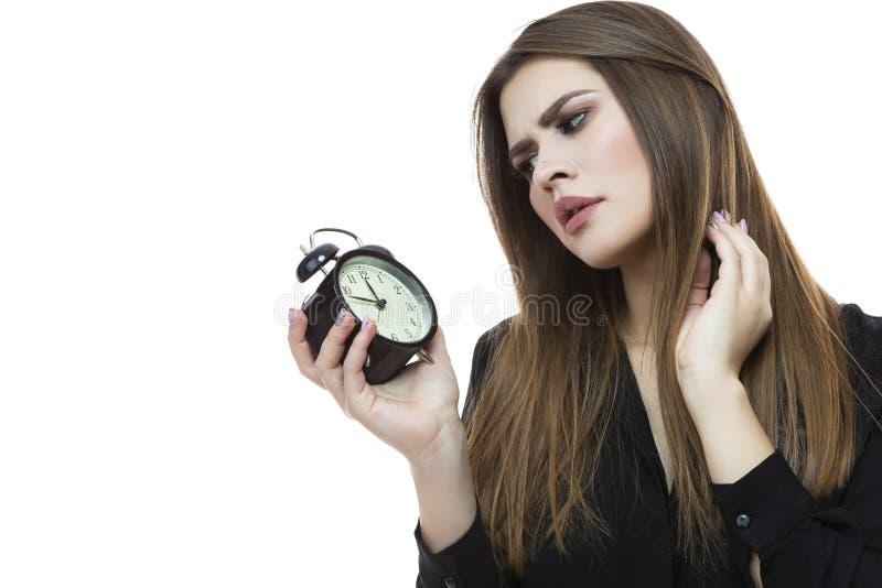 Portret van Kaukasisch Wijfje die Tijd met Grote klok controleren Tegen wit royalty-vrije stock afbeeldingen