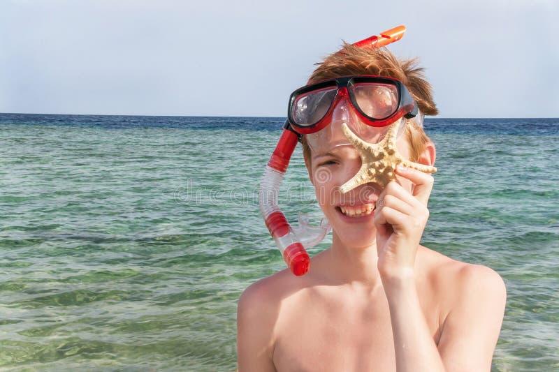 Portret van Kaukasische jongen bij het strand die met masker snorkelen en royalty-vrije stock afbeelding
