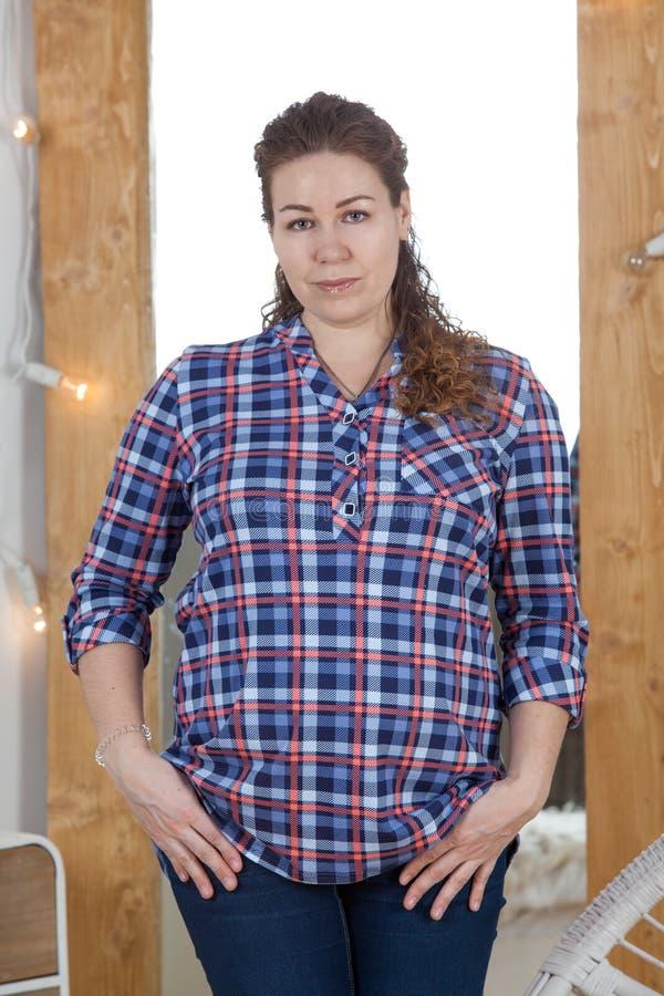 Portret van Kaukasische zwangere vrouw, gekleed plaidoverhemd, die camera, krullend haar bekijken royalty-vrije stock fotografie
