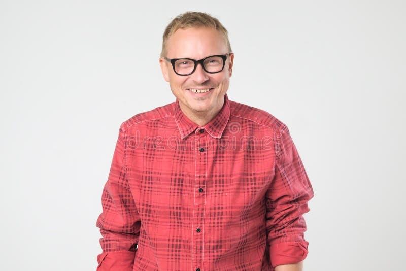 Portret van kerel die denimoverhemd, lachen dragen, geïsoleerd over witte achtergrond stock foto's