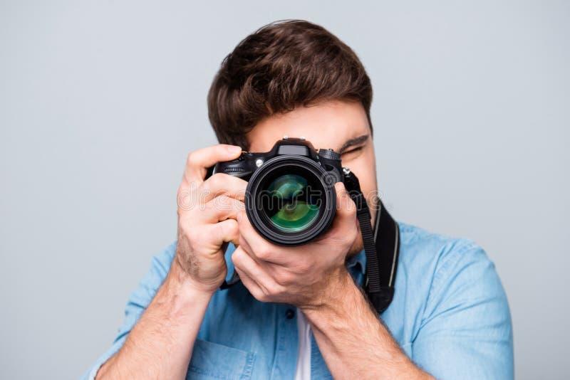 Portret van kerel in jeansoverhemd die fotocamera bekijken, het schieten stock foto's