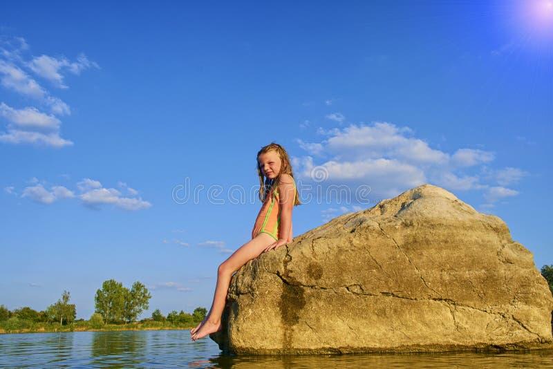 Portret van kind het blonde meisje stellen in zwempak op rotsen binnen het meer bij zonsondergang De zomer en gelukkig kinderjare royalty-vrije stock foto