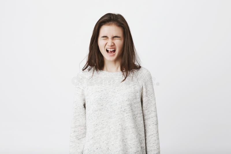Portret van kinderachtige tiener die op het punt staat te schreeuwen, met gesloten ogen zich te bevinden en luid gillen uit Meisj stock afbeeldingen