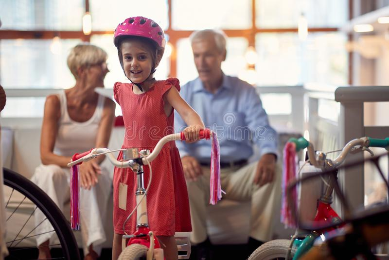 Portret van kindmeisje dat op fiets in fietswinkel zit stock afbeelding