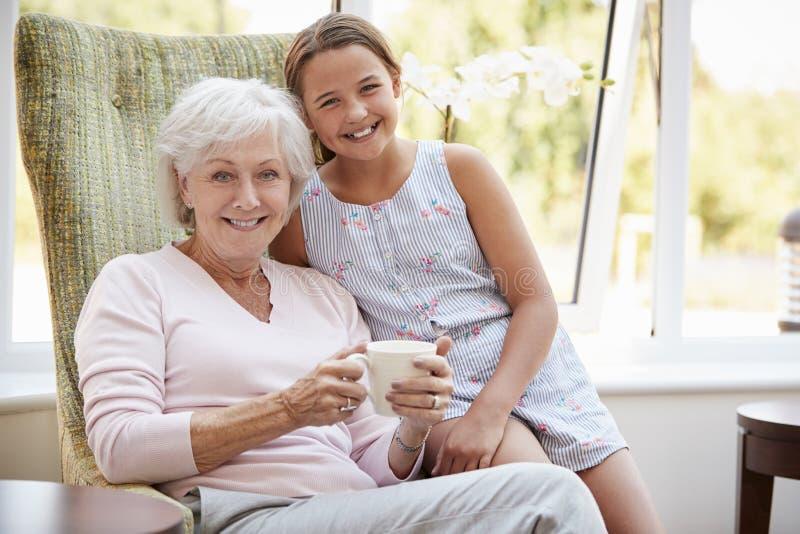 Portret van Kleindochter Bezoekende Grootmoeder in Zitkamer van Pensioneringshuis stock foto's