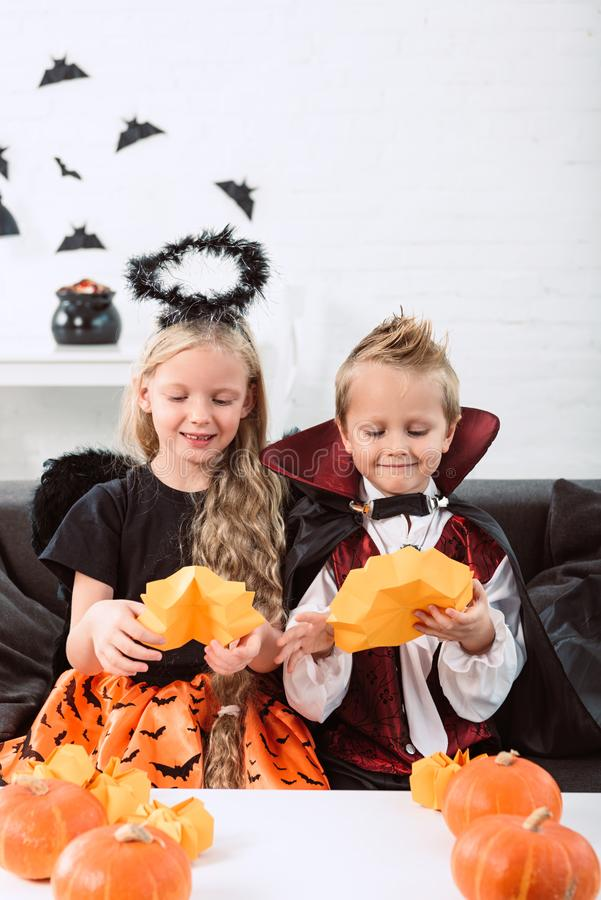 portret van kleine siblings in Halloween-kostuums die op bank bij lijst met pompoenen zitten stock foto