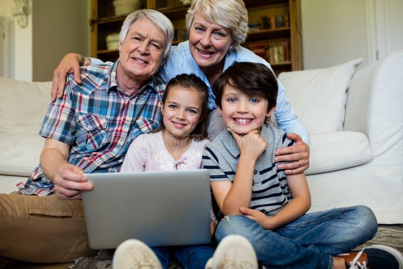 Portret van kleinkinderen en grootouders met laptop in woonkamer stock fotografie